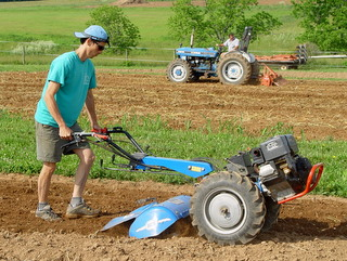 John Rodgers (foreground) cultivates a market garden plot using a walk-behind tractor while Tony Silvernail performs the same task in a small farm plot with a 4-wheeled tractor.