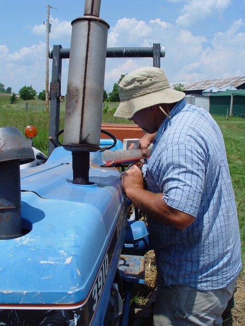 Tony Silvernail uses a graduated cylinder to measure the amount of diesel fuel needed to top off the tractor's tank after a field operation.